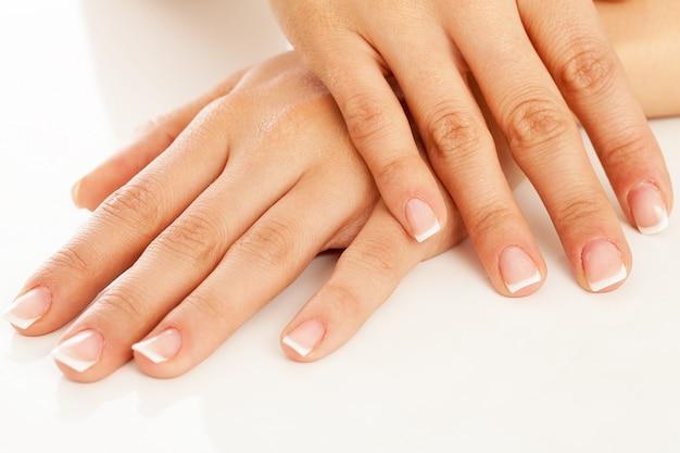 Mãos de mulher jovem com manicure francesa