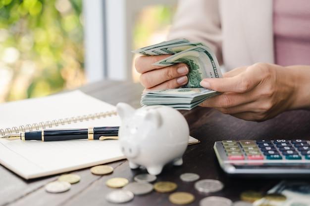 Mãos de mulher jovem, contando-nos notas de dólar. economizando dinheiro e conceito financeiro