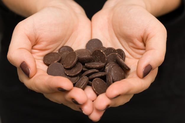 Mãos de mulher jovem em forma de coração com chocolate amargo para fazer bolos caseiros