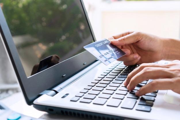 Mãos de mulher jovem, navegando no site de compras on-line, mantendo o cartão de crédito