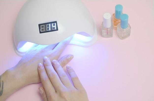 Mãos de mulher jovem no procedimento de manicure close-up no fundo rosa pastel