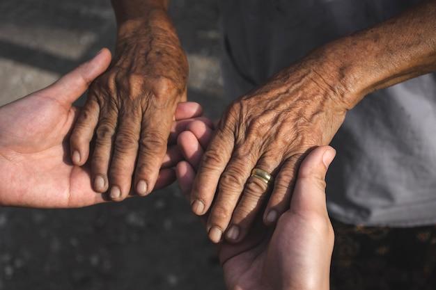 Mãos de mulher jovem segurando as mãos de uma pessoa idosa.