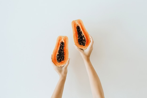 Mãos de mulher jovem segurando um mamão laranja tropical exótico. vegetariano sazonal minimalista
