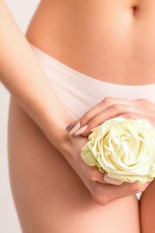 Mãos de mulher jovem segurando uma flor branca cobrindo a zona do biquíni depilada isolada no fundo branco do estúdio.