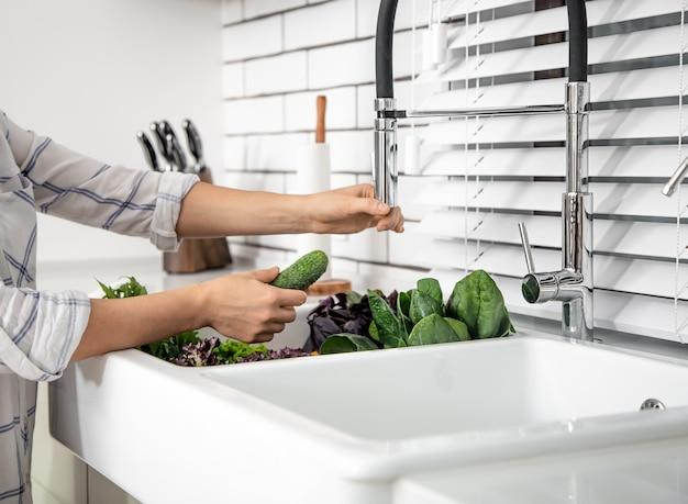 Mãos de mulher lavando alface na pia da cozinha close-up.