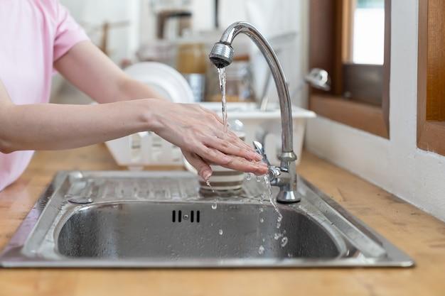 Mãos de mulher lavando-se com água limpa na cozinha em casa durante uma crise de coronavírus ou surto de covid-19.