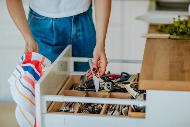 Mãos de mulher, limpando o conjunto de cozinha em caixa de gaveta