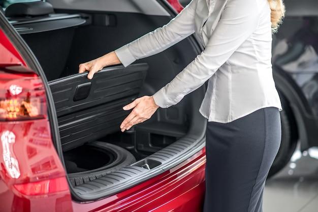 Mãos de mulher mostrando dispositivo de porta-malas aberto