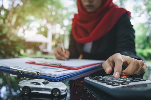 Mãos de mulher muçulmana de negócios escrevendo e calculando cotações de seguro de carro
