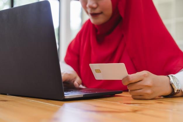 Mãos de mulher muçulmana segurando o cartão de crédito e usando o laptop para compras on-line. sexta-feira negra e cyber segunda-feira compras online conceito