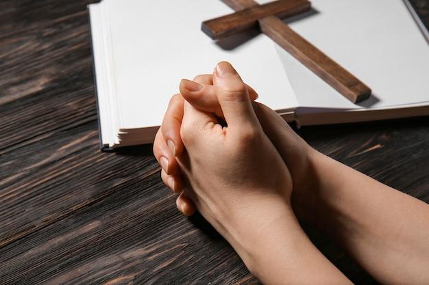 Mãos de mulher orando, bíblia e cruz no espaço de madeira