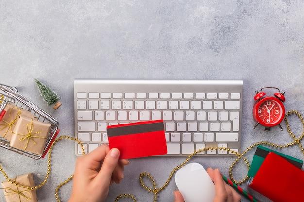 Mãos de mulher, pagando com cartão de crédito para o natal apresenta espaço de vista superior para texto