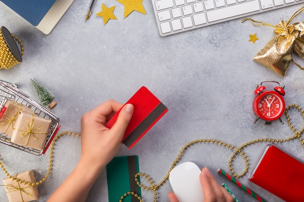 Mãos de mulher, pagando com cartão de crédito vista superior de presentes de natal online
