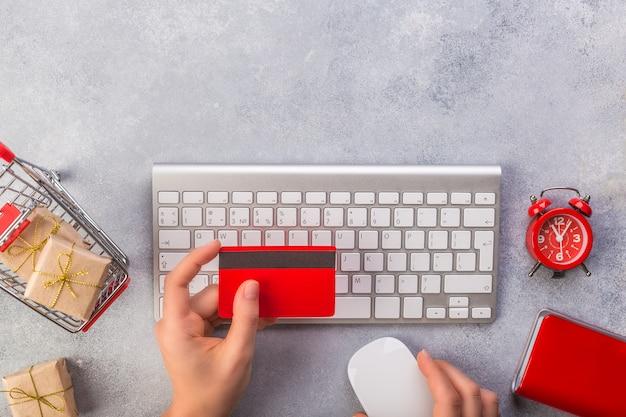Mãos de mulher, pagando com cartão de crédito vista superior do relógio do teclado on-line em cinza