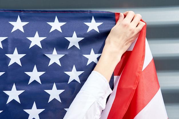 Mãos de mulher, pendurando a bandeira dos eua em uma parede cinza, conceito de dia da independência dos eua