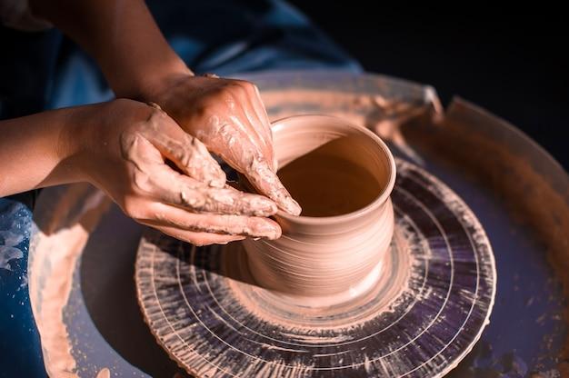 Mãos de mulher potter criando pratos