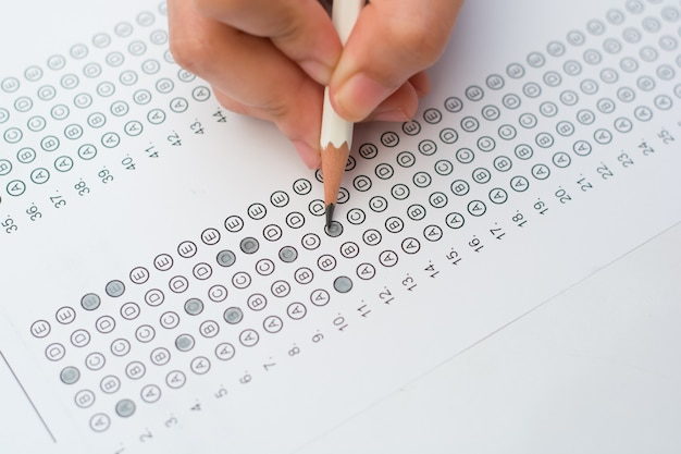 Mãos de mulher, preenchendo o formulário de teste padronizado