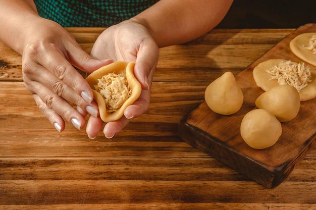 Mãos de mulher preparando croquete brasileiro