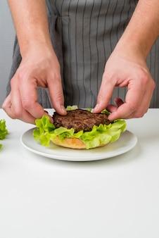 Mãos de mulher preparando um hambúrguer