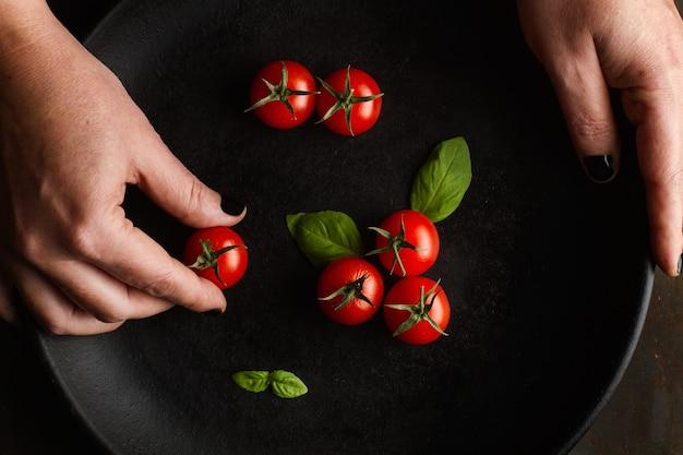 Mãos de mulher preparando um prato com tomate cereja