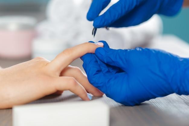 Mãos de mulher recebendo uma manicure em salão de beleza