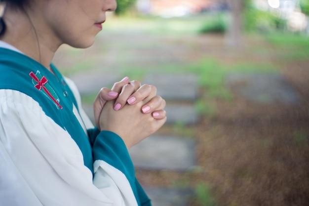 Mãos de mulher rezando com uma bíblia de joelhos ao ar livre