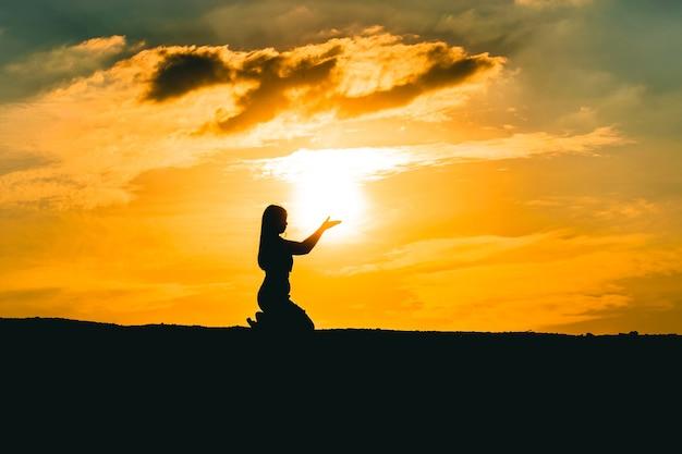 Mãos de mulher rezando pela bênção de deus no fundo do pôr do sol