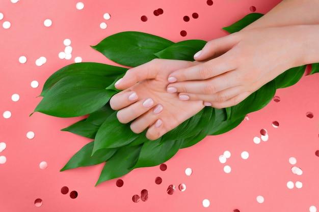 Mãos de mulher rosa com fundo de folhas verdes e confetes