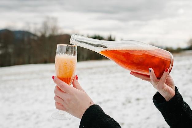 Mãos de mulher segura uma garrafa de champanhe e derrama em um copo no fundo das montanhas de inverno.