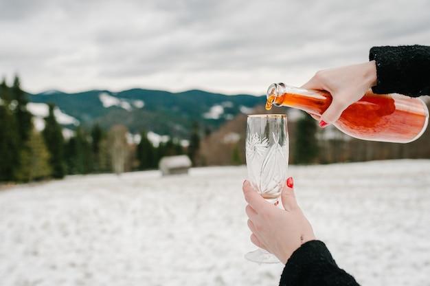 Mãos de mulher segura uma garrafa de champanhe e derrama em uma taça nas montanhas de inverno. temporada de feriados.