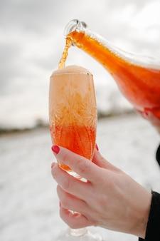 Mãos de mulher segura uma garrafa de champanhe e derrama em uma taça nas montanhas de inverno.