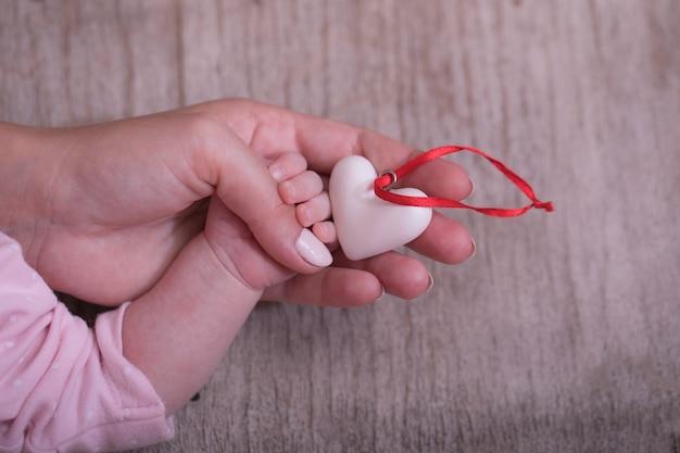 Mãos de mulher segurando a mão da criança com um coração. dia humanitário mundial