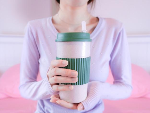 Mãos de mulher segurando a xícara de café. menina na camisola segurando caneca.