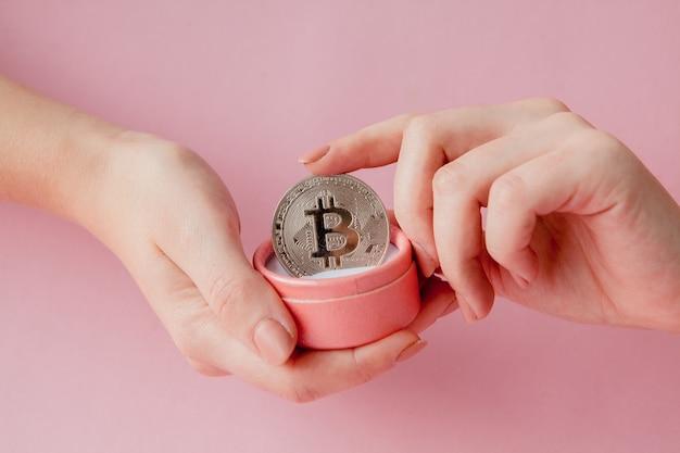 Mãos de mulher segurando bitcoin em uma caixa de presente rosa em um fundo rosa, símbolo do dinheiro virtual