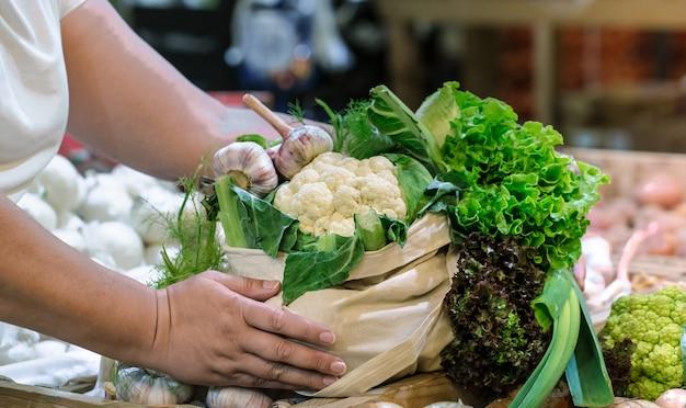 Mãos de mulher segurando brócolis fresco maduro orgânico, salada com verduras e legumes em um saco de algodão no mercado do fazendeiro de fim de semana