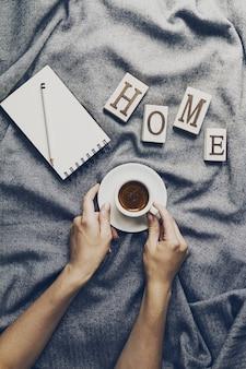 Mãos de mulher segurando café espresso saboroso em copo pequeno em xadrez cinza. conceito de casa. vista do topo.