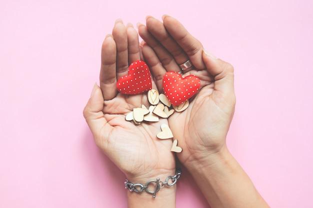 Mãos de mulher segurando corações. conceito de amor e dia dos namorados no fundo rosa