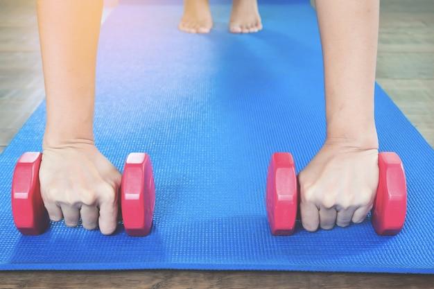 Mãos de mulher segurando dumbbells com pose de prancha completa sobre tapete de yoga de cor azul, visão frontal, conceito de estilo de vida saudável com espaço de cópia