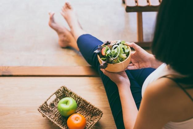 Mãos de mulher segurando e comendo salada saudável no café da manhã