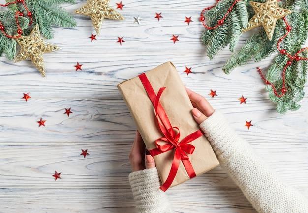 Mãos de mulher segurando embrulhado presente de natal com decoração de estrelas de árvore e sparklins de abeto