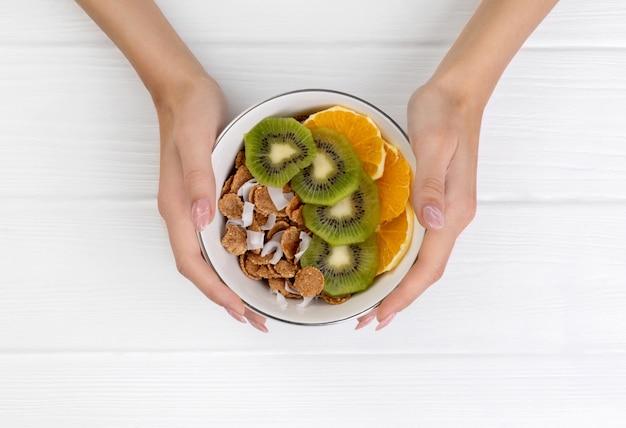 Mãos de mulher segurando flocos multigrain com frutas laranja e kiwi e coco na tigela