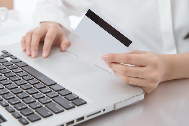 Mãos de mulher segurando o cartão de crédito e usando o laptop. compras on-line do conceito.