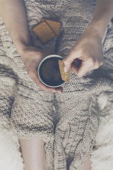 Mãos de mulher segurando o expresso café quente quente em copo de cerâmica com biscoito sentado na cama com xadrez. conceito de casa. vista do topo.