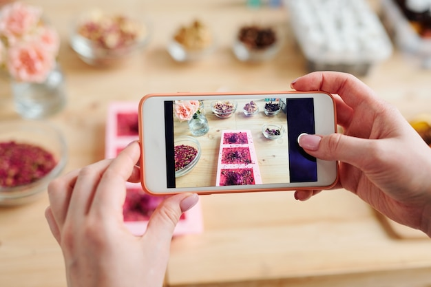 Mãos de mulher segurando o smartphone sobre a mesa enquanto tira foto de sabonete artesanal em moldes de silicone