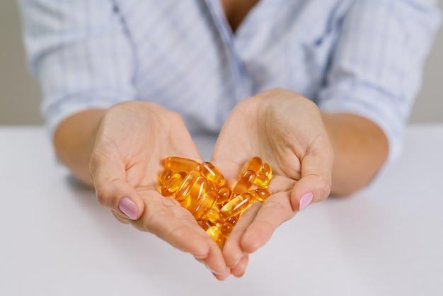 Mãos de mulher segurando óleo de peixe omega-3 cápsulas