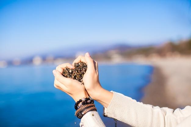 Mãos de mulher segurando pedras pequenas formam forma de coração