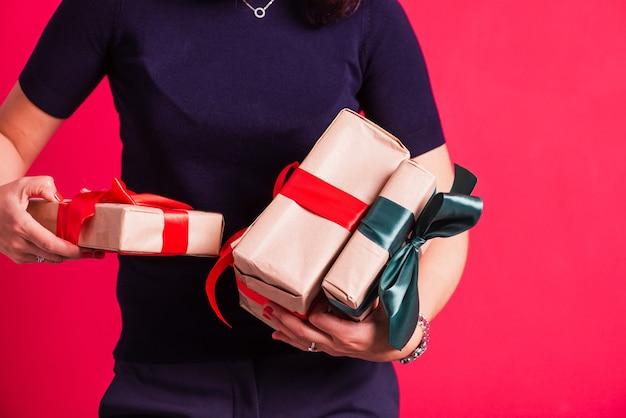 Mãos de mulher segurando três presentes no fundo rosa do estúdio