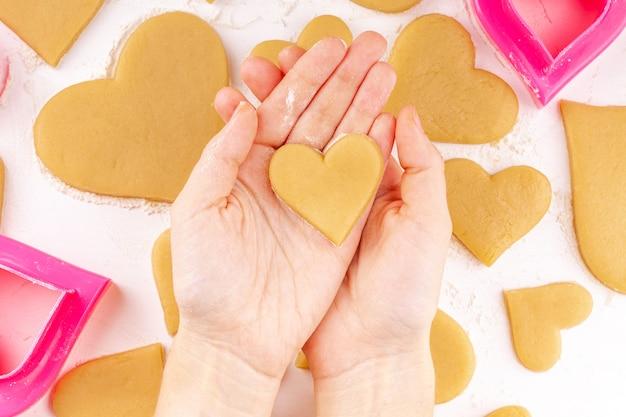 Mãos de mulher segurando um biscoito em forma de coração cru