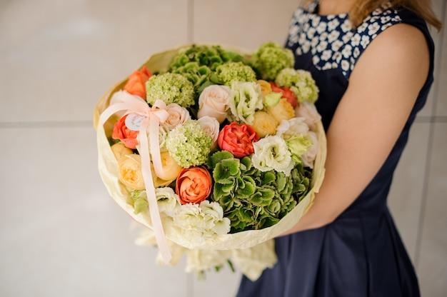 Mãos de mulher segurando um buquê colorido de flores