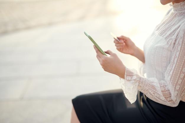 Mãos de mulher segurando um cartão de crédito e usando o celular para fazer compras online ao ar livre